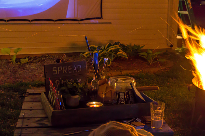 A s'mores kit on a table next to a fire pit while an outdoor movie plays on a screen in the background.