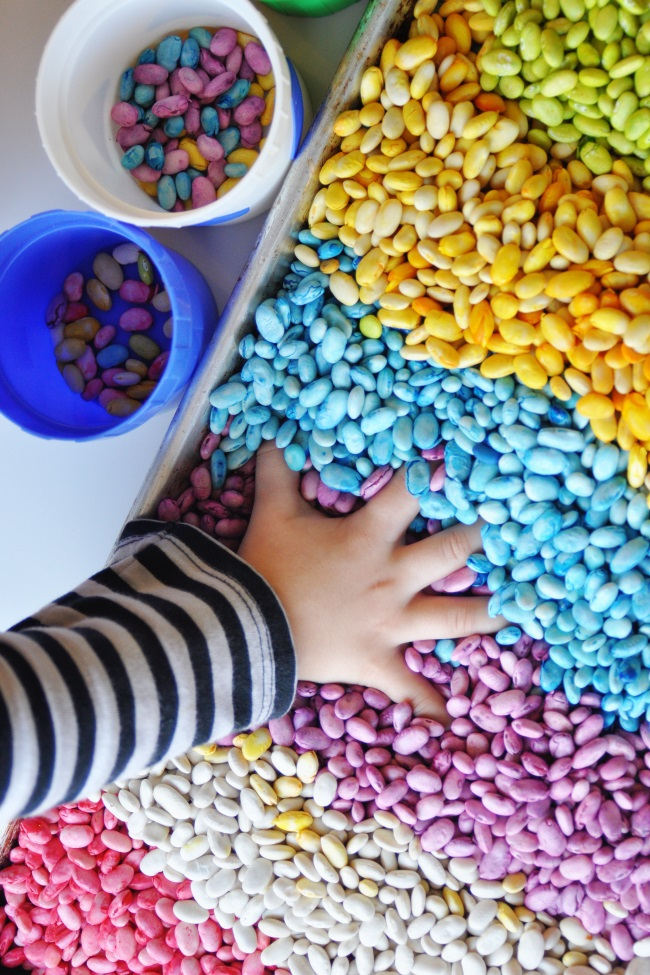 Scented rainbow beans in a shallow sensory bin from Kids Activities Blog