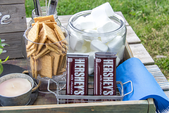 Hershey's chocolate bars, marshmallows and Graham crackers in containers for an outdoor movie night with s'mores.