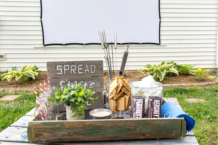 A box containing s'mores ingredients with an outdoor movie screen in the background for a backyard family movie night.