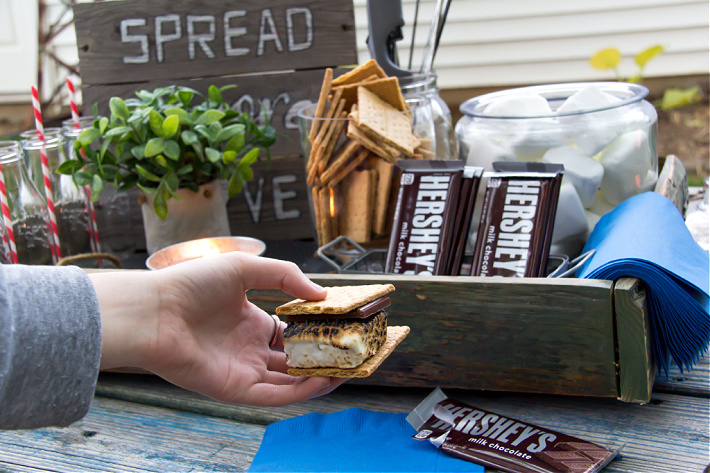 A hand holding s'mores in front of a backyard movie night s'mores kit.