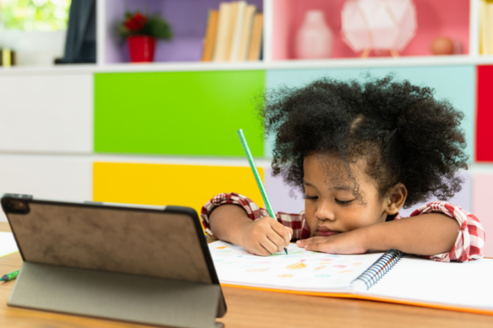 Interactive learning through computers for kids - Kids Activities Blog - child following along in a workbook while teacher uses virtual classroom