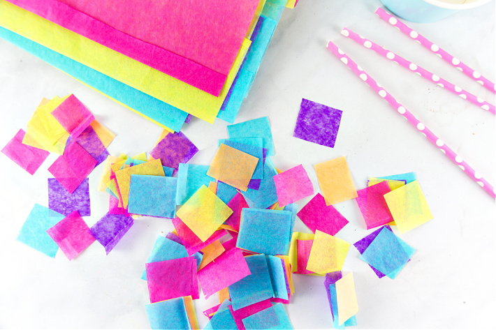 Colorful tissue paper cut into squares for making a paper mache craft with kids.
