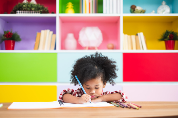 10 Awesome Free Handwriting Worksheets For Kids - child sitting at table practicing handwriting on worksheet in front of colorful bookcase