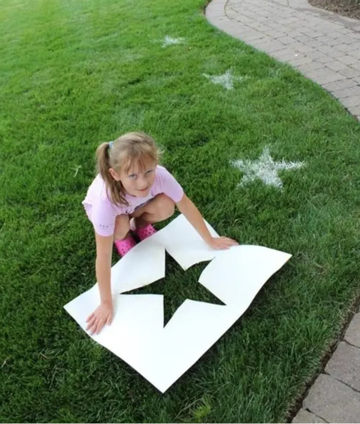 Make patriotic lawn stars from Pink and Green Mama - child making white stars on grass with a template