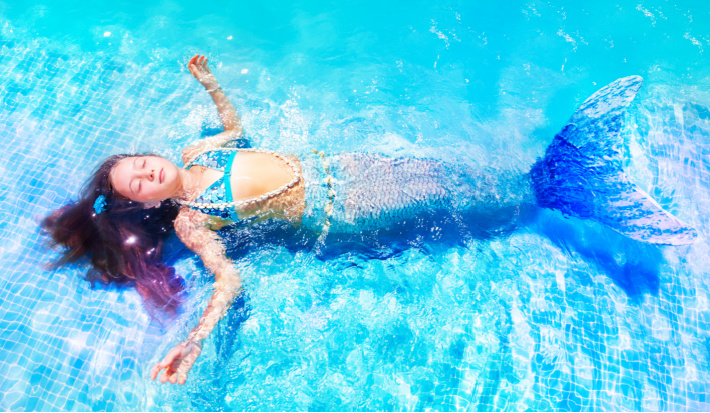 Swimmable fabric mermaid tail worn by child in pool laying in sun with sparkling water and scale patterns in colors of blue and purple