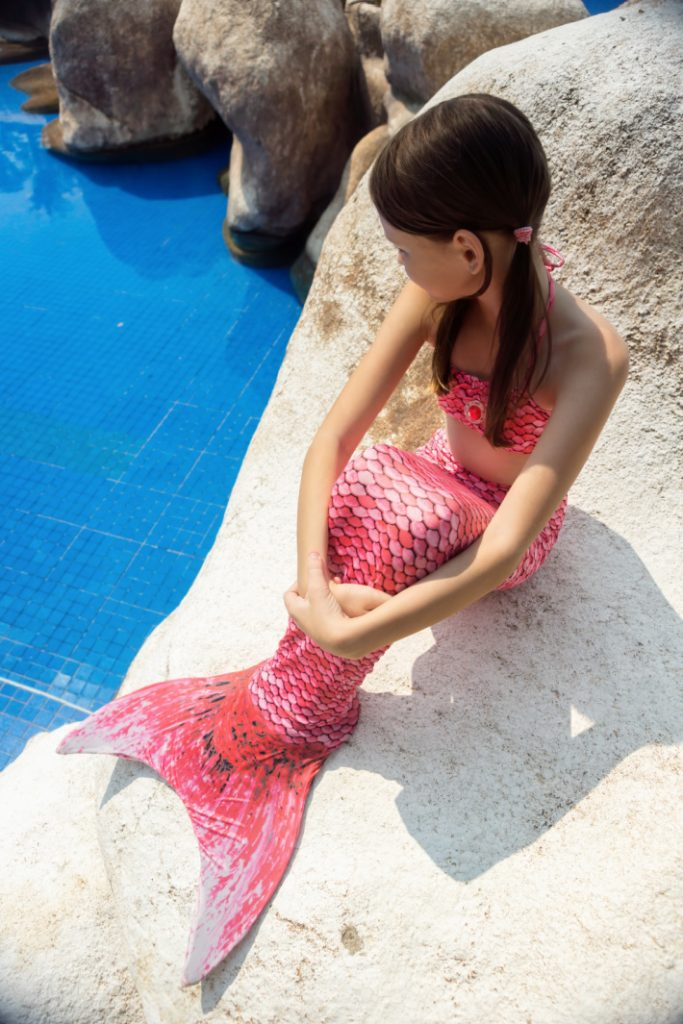 Child in swimmable fabric mermaid tail sitting on a rock next to the pool water.