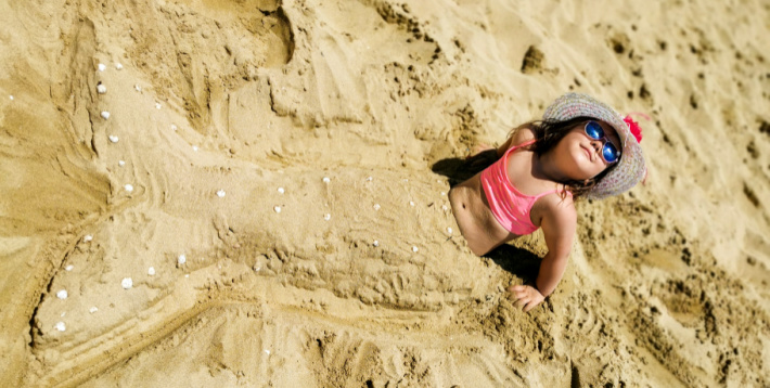More mermaid fun from Kids Activities Blog - girl in sand with mermaid tail outline made of sand