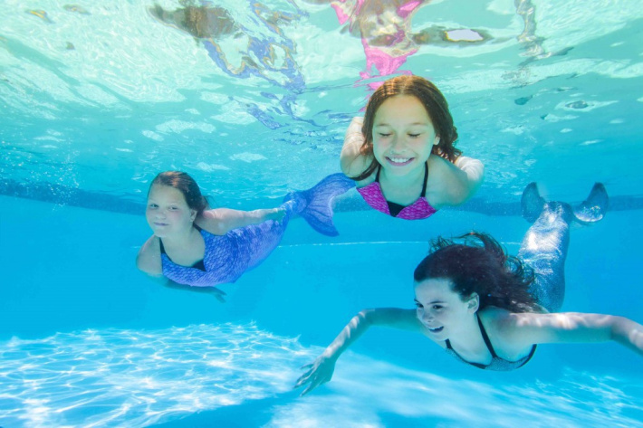 fin fun mermaid tails in action from fin fun files - three kids swimming in fabric mermaid tails underwater in public pools.