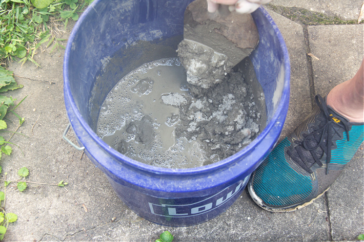 Mixing fast-setting concrete mix in a bucket with water.