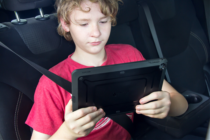 Boy watching a show on an iPad on a road trip.