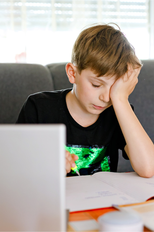 ADHD Can make learning frustrating as seen with this boy in a green and black shirt as he tries to do his homework.