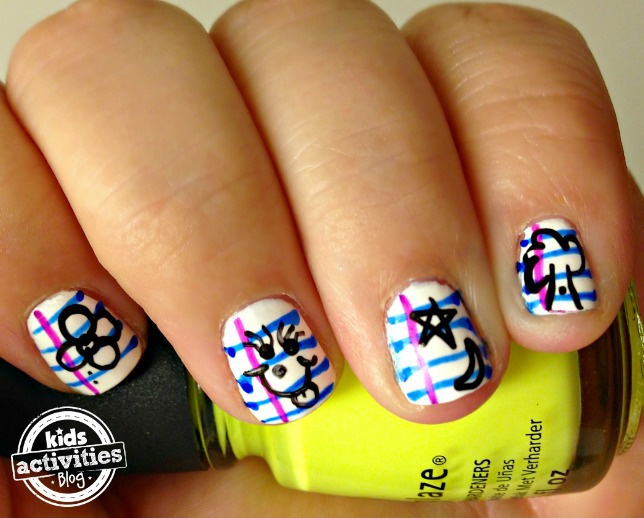 Back to school nails - notebook nail art - Kids Activities Blog - finished notebook nails holding yellow polish
