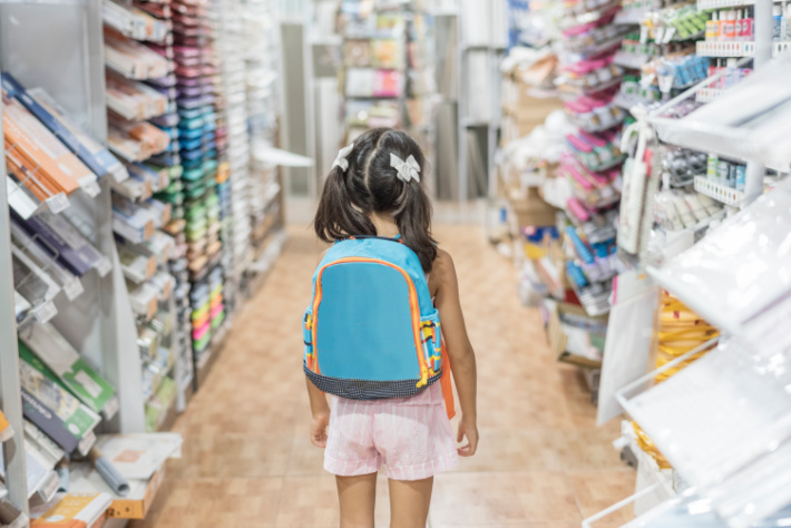 Child on the aisle of school supplies for back to school shopping wearing backpack
