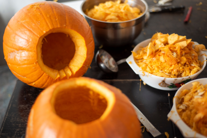 Cutting the top off pumpkin with notch and removing guts - Kids Activities Blog