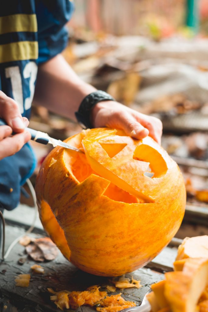 How to carve a pumpkin - Kids activities blog - kid carving a jack o lantern with a knife