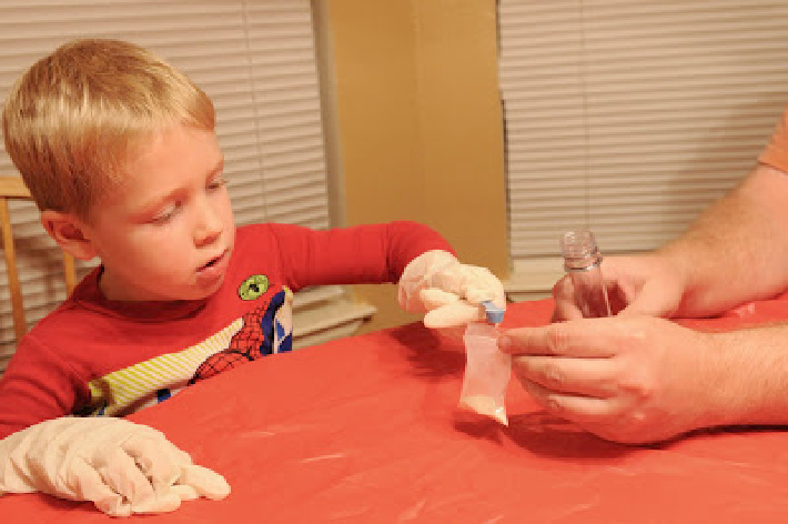 Putting the zinc sulfide in the test tube with gloves on - Kids Activities Blog