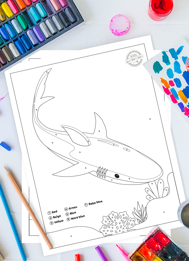 Shark color by number pdf printable from Kids Activities Blog shown on a white background with colored pencils and paint