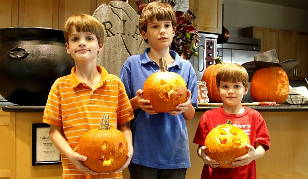 three kids holding carved pumpkins created from stencils at a pumpkin carving class