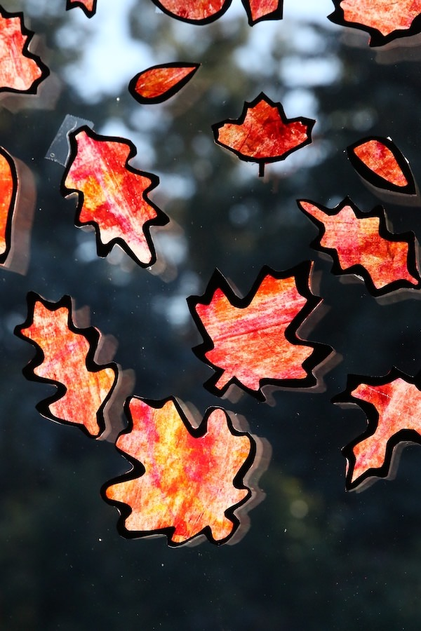 autumn leaf suncatcher craft for kids shown with orange yellow and red leaves on a window from Happy Hooligans