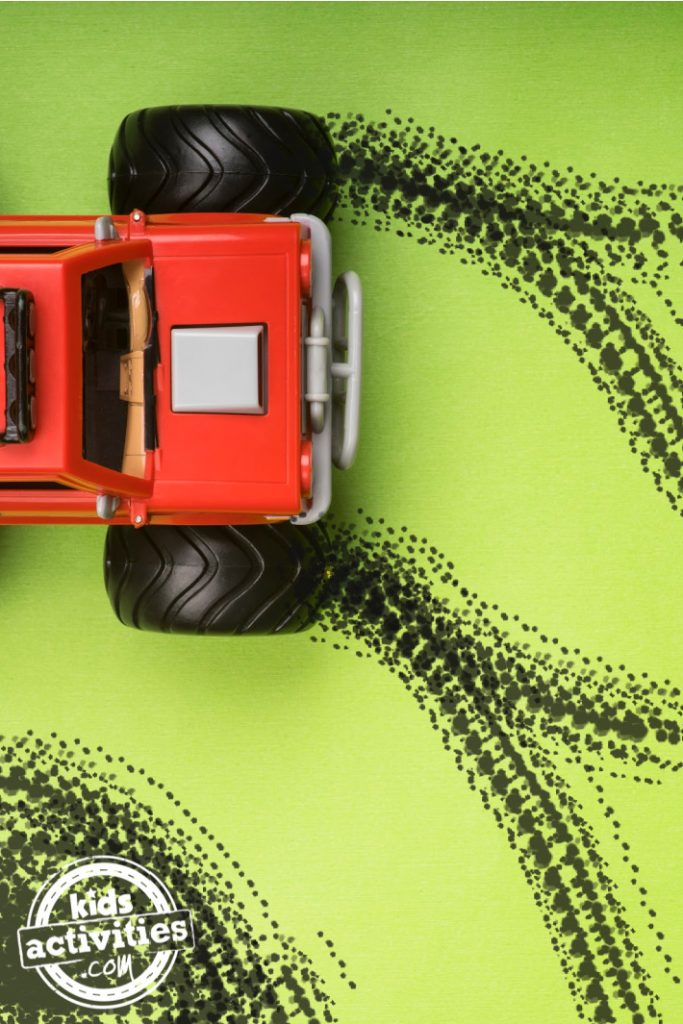 Painting with Monster Trucks preschool art activity for kids - monster truck shown with painted black tire tracks and Kids Activities Blog logo