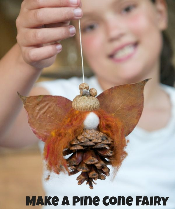 Make a leaf and pinecone fairy from The Magic Onions - finished fall craft shown with child holding leaf fairy hanging from string