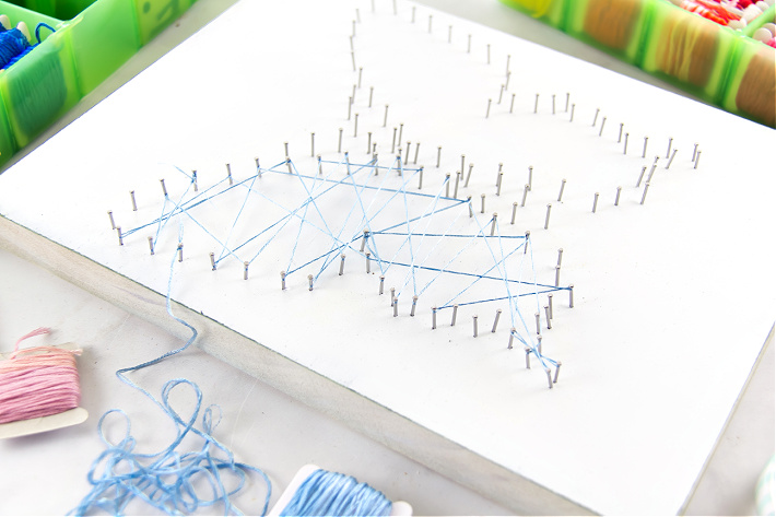 A DIY string art butterfly being made with blue embroidery thread.