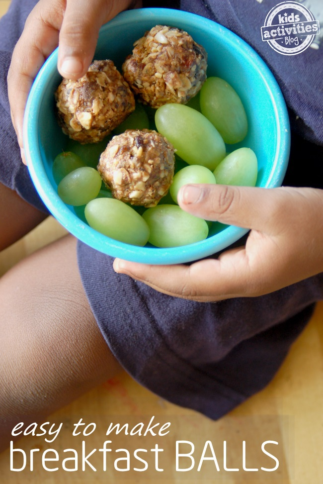 energy balls as a snack for picky eaters - shown are breakfast balls in a bowl with grapes on child lap