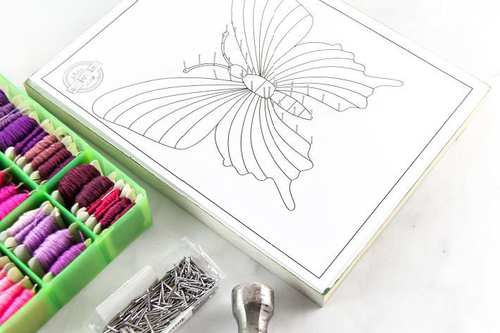 Nails being hammered around a butterfly outline to make string art. Coloring pages make great string art templates.