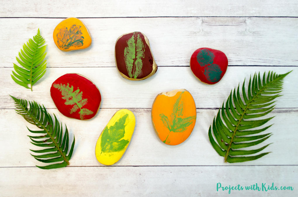 Painted rocks with leaf stamps on them from Projects with Kids - fern leaves shown with multiple colored rocks stamped with fall leaves