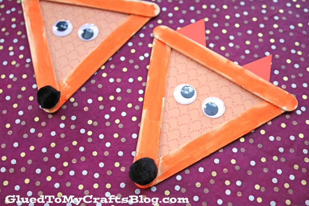 popsicle stick fox craft for kids from Glued to My Crafts Blog - two finished popsicle stick foxes shown with googly eyes