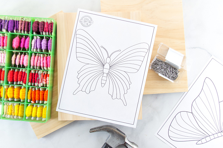 Supplies to make butterfly string art including a butterfly outline coloring page, embroidery thread, wood, and nails.