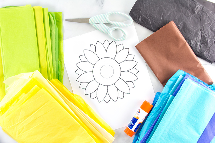 Supplies to make a tissue paper sunflower including tissue paper in yellow, green, blue, black, and brown and a sunflower printable.