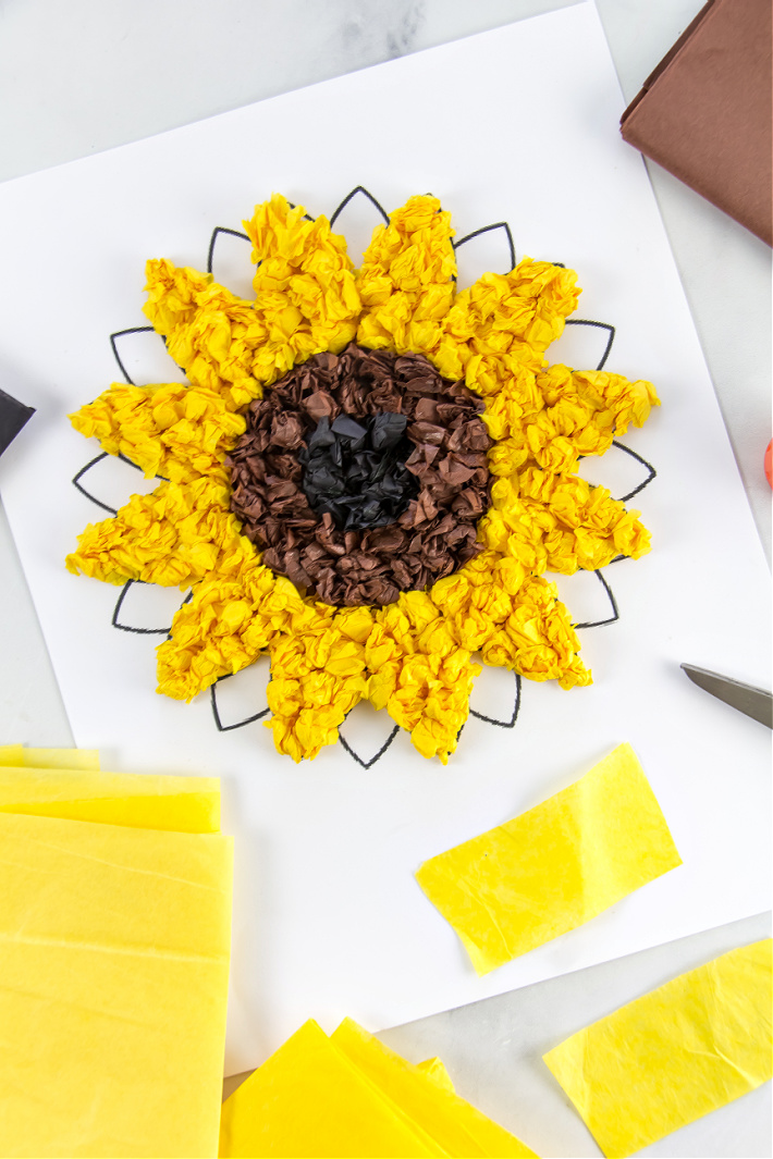 A printable sunflower being covered in balls of yellow, brown, and black tissue paper to make sunflower art.