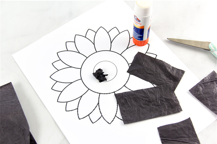 Small pieces of black tissue paper being cut up and scrunched into a ball to make the center of a sunflower.