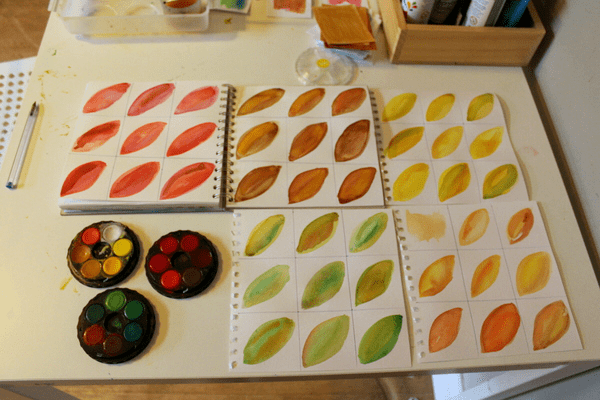 painted watercolor leaves on paper shown with paints from Nuturestore