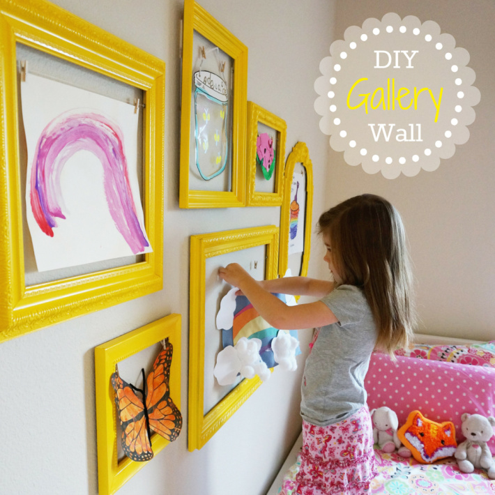 DIY Gallery Wall for kids artwork from the caterpillar years - child hanging art inside painted frames on her bedroom wall