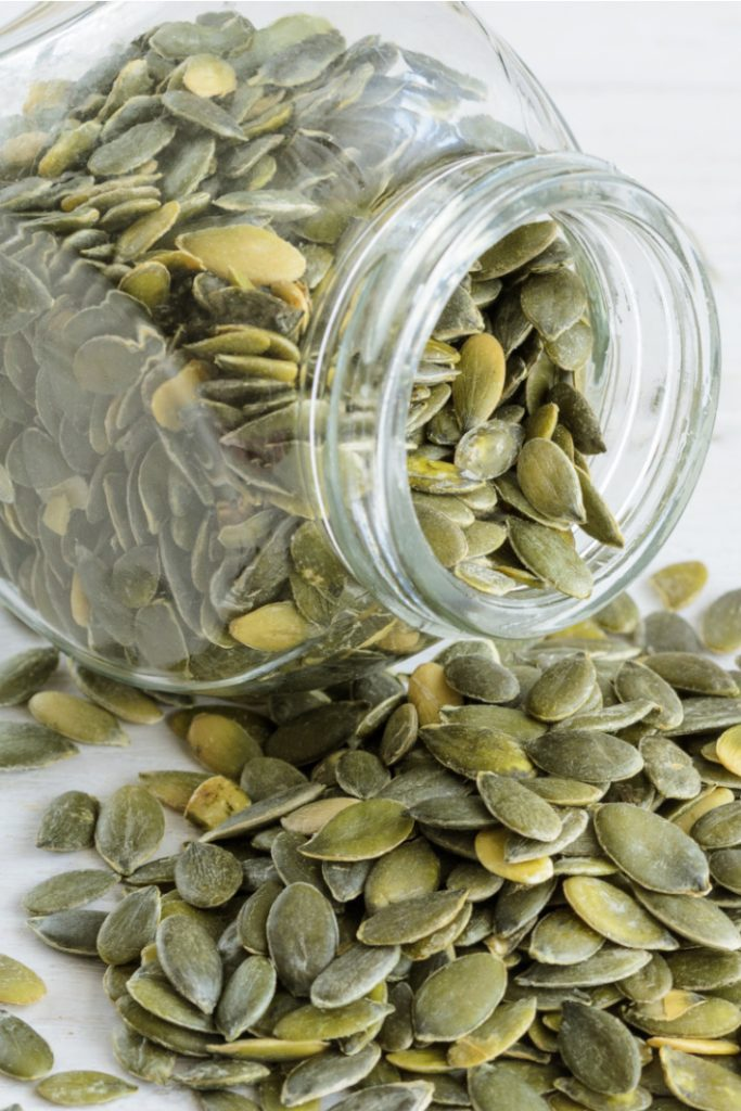 Easy Roasted Pumpkin seed recipe for kids - Kids Activities Blog - jar with pumpkin seeds falling out