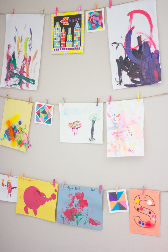Kids artwork gallery wall from Design Improvised using clothesline and clothespins - wall with colorful kids art displayed