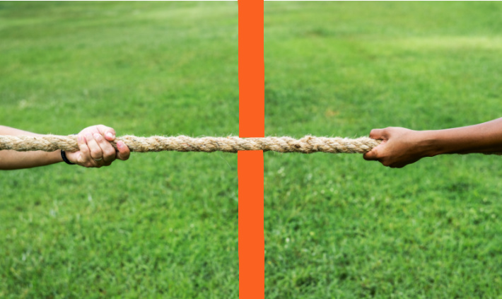 Tug of war with two people pulling on the rope with an orange line of tape simulated