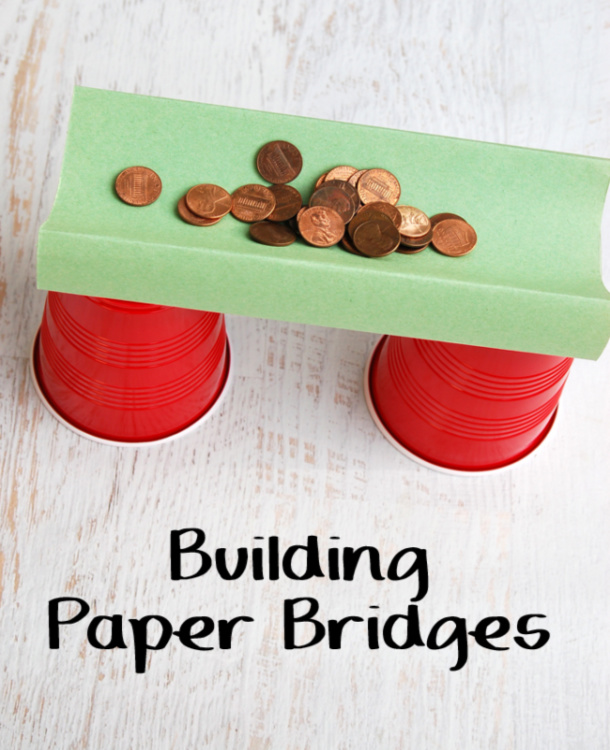 Paper bridge science activity with 2 red paper cups, a green piece of paper that is holding 23 pennies on it.