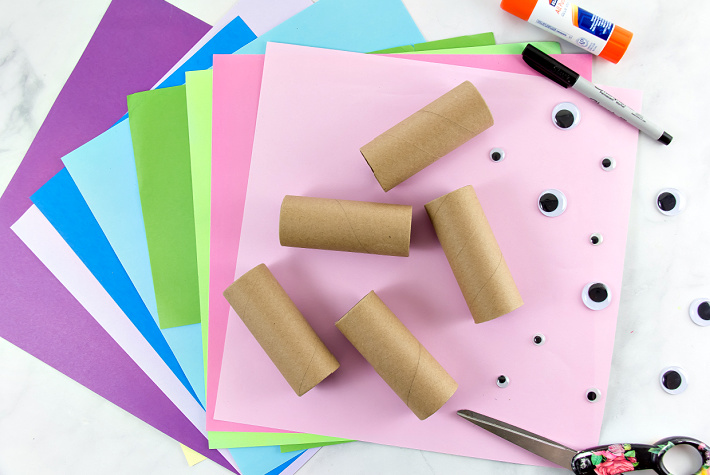 Colorful scrapbook paper and googly eyes to make monster toilet paper roll crafts for kids