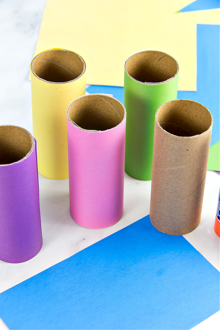 Toilet paper rolls covered in colored scrapbook paper for a kids craft.