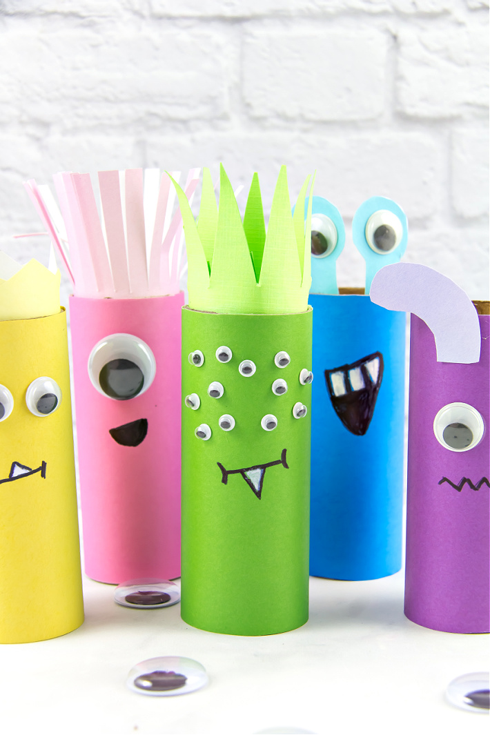 Bright and colorful toilet paper roll monster crafts for kids using scrapbook paper and googly eyes.