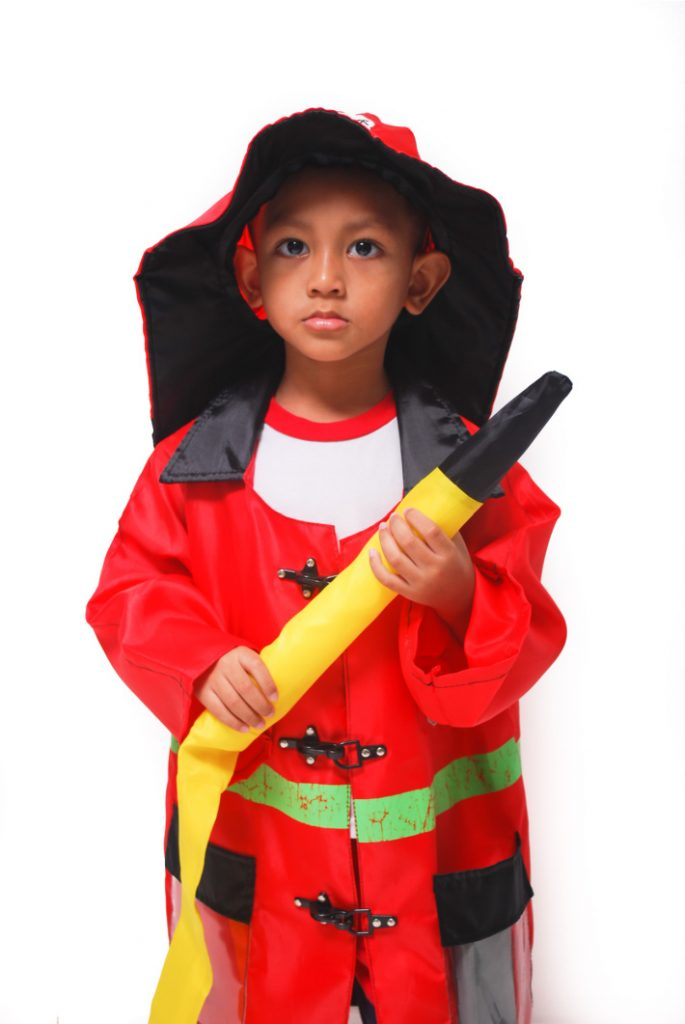 Choose a firefighter theme for your family Halloween costume - little child holding a fire hose dressed in fire fighter costume