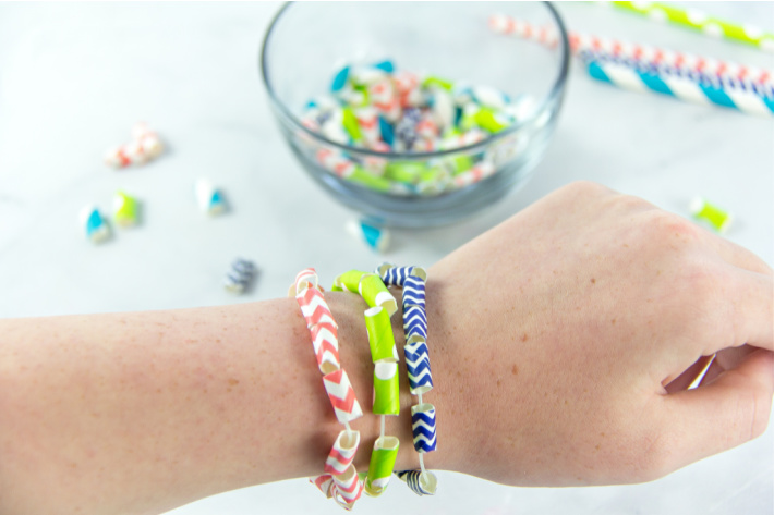 How to make paper beads is included in The Big Book of Kids Activities as one of the crafts featured - hand with paper bead bracelet pictured