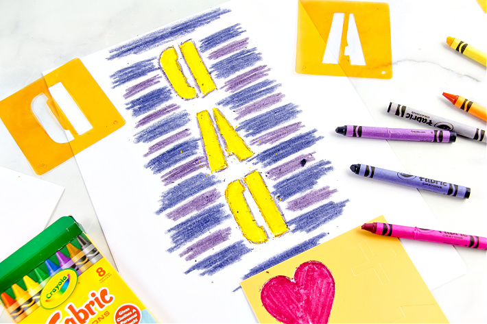 A picture being drawn on paper using fabric crayons.