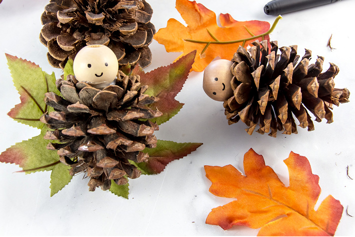 Fall leaves glued to pinecones to make fairy wings.