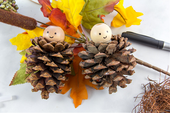 pinecones with wood beads on top with faces drawn on