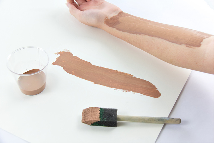 An arm painted with brown paint to stamp a tree trunk on paper.